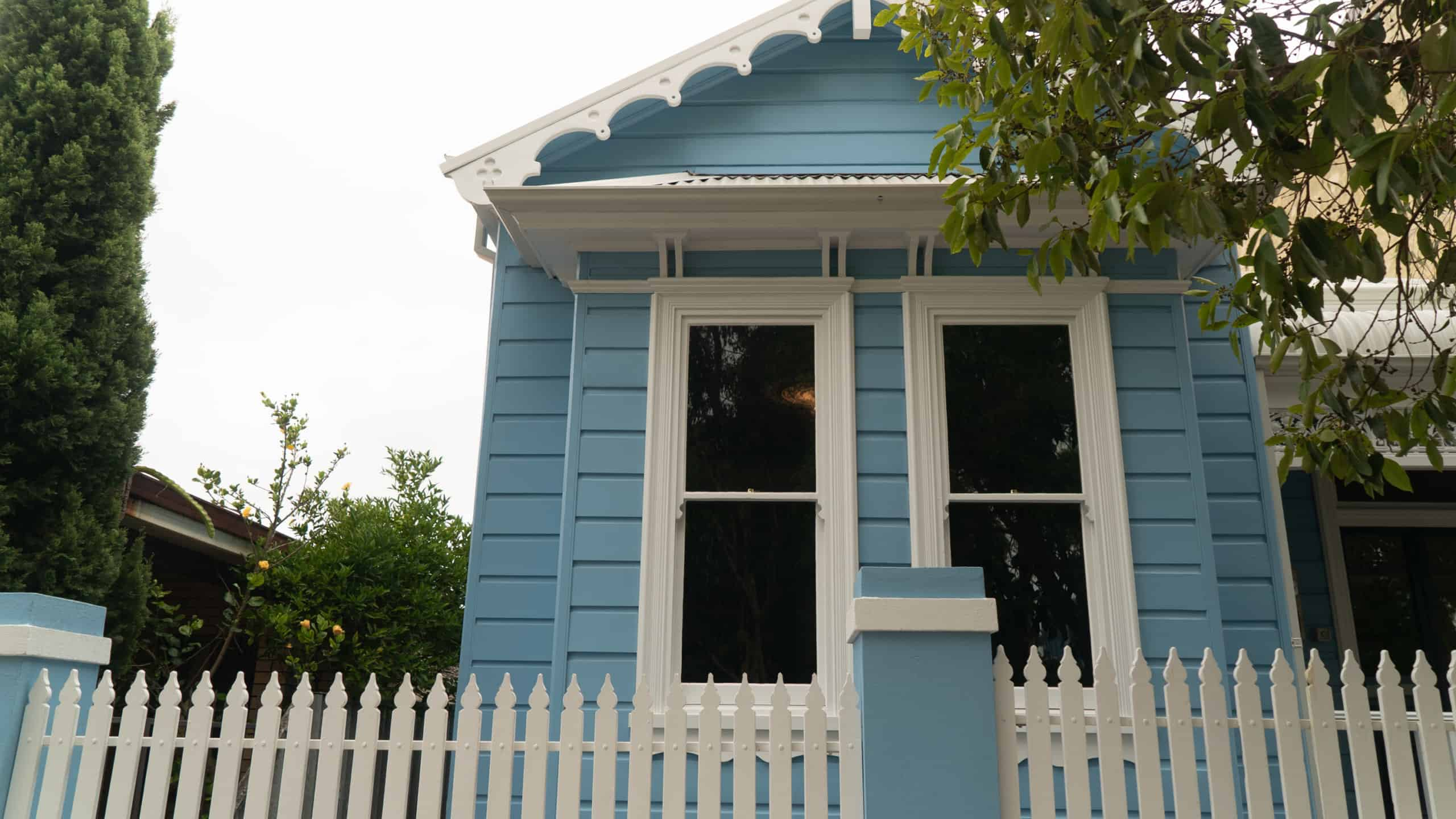 The exterior of a freshly painted heritage property with a white fence